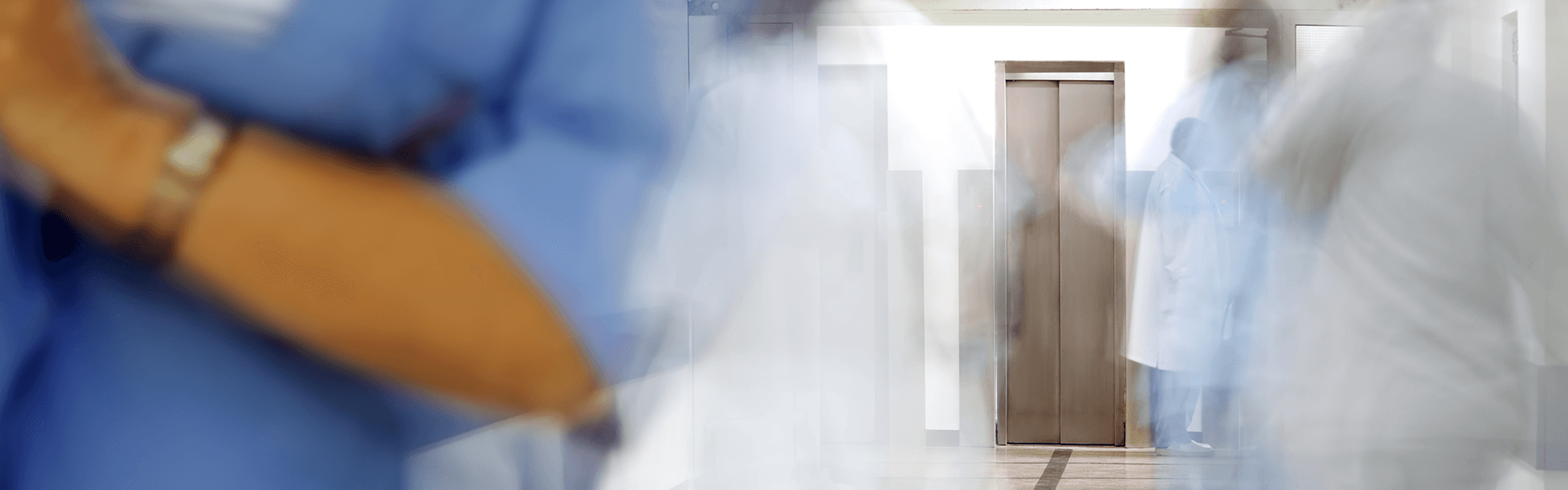 Blurred figures of doctors and nurses in a hospital corridor